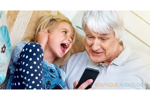 Grandad & Grandaughter listening to phone with earphones